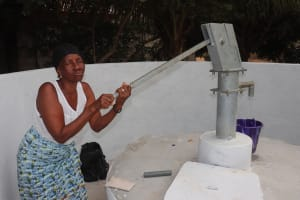 The Water Project: Lungi, New York, Robis, #7 Masata Lane -  Woman Collects Water After Pump Installation
