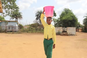 The Water Project: Lungi, Tintafor, Sierra Leone Church Primary School -  Student Carrying Water