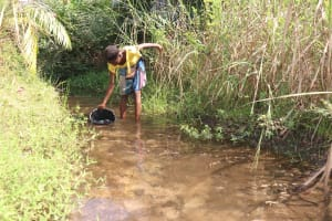 The Water Project: Lokomasama, Bompa Morie Village -  Community Member Collecting Water