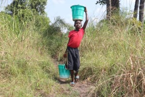 The Water Project: Lokomasama, Bompa Morie Village -  Community Member Carrying Water
