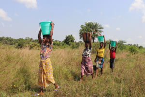 The Water Project: Lokomasama, Bompa Morie Village -  Community Members Carrying Water