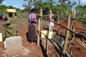 The Water Project: Kinuma Kyarugude Community -  Kinuma Kyarugudde People Collection Water At The Waterpoint