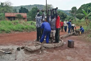 The Water Project: Kabo Village -  Community Assisting The Removal Of The Old Well Pipes
