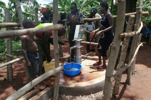 The Water Project: Kabo Village -  People Get Water From Their Rehabilitated Well