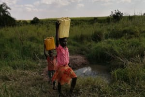 The Water Project: Nsamya Nusaff II Well -  Children Carry Water Home