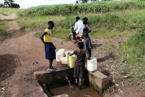 The Water Project: Nsamya Nusaff II Well -  Collecting Water At The Spring