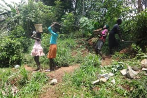 The Water Project: Shihome Community, Peter Majoni Spring -  Community Members Bring Materials To Work Site