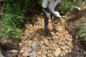 The Water Project: Musango Commnuity, Wabuti Spring -  Layering Smaller Stones