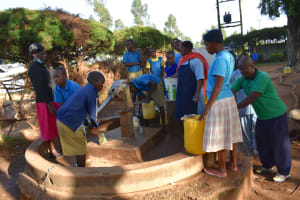 The Water Project: Ibokolo Primary School -  Pupils Collect Water As Community Members Wait