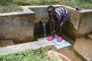 The Water Project: Ewamakhumbi Community, Mukungu Spring -  Jeremiah Rinsing Off At The Spring