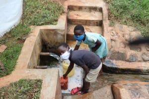 The Water Project: Mushina Community, Shikuku Spring -  Marion And A Boy Drawing Water