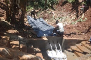 The Water Project: Shihome Community, Peter Majoni Spring -  Layering Tarp Over Stones