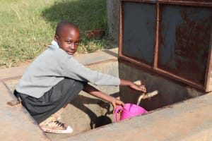 The Water Project: Khabukoshe Primary School -  Mitchelle Fetching Water From The Tank For Use