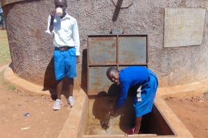 The Water Project: Sango Primary School -  Pauline And Student Brian At The Tank