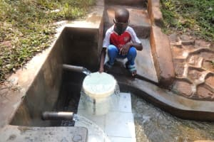 The Water Project: Rosterman Community, Kidiga Spring -  Festus Fetching Water