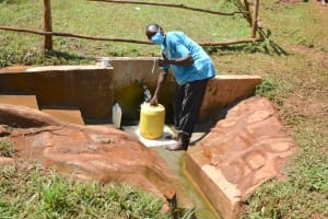 The Water Project: Mutao Community, Kenya Spring -  George Shikhule Fetches Water