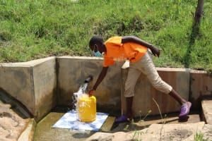 The Water Project: Ikonyero Community, Amkongo Spring -  Reagan Fetching Water
