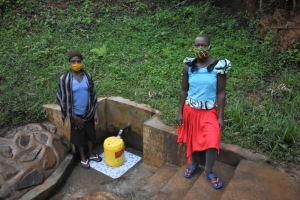The Water Project: Bumira Community, Imbwaga Spring -  Gertrude And Teenager Quinta Fetching Water