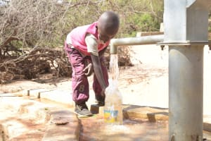 The Water Project: Katovya Community A -  Child Fills Container At The Well A Year Later