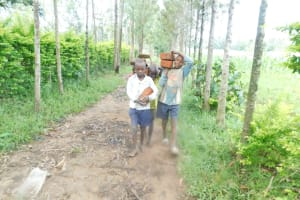 The Water Project: Shianda Township Community, Olingo Spring -  Teamwork To Bring Materials To Site