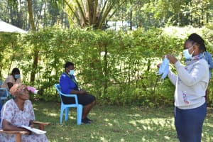 The Water Project: Shianda Township Community, Olingo Spring -  Trainer Joyce Leads Mask Making Session