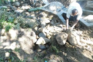 The Water Project: Shianda Township Community, Olingo Spring -  Backfilling With Large Rocks