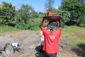 The Water Project: Machemo Community, Boaz Mukulo Spring -  Community Members Deliver Bricks