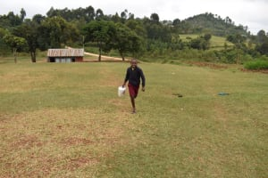 The Water Project: Givudemesi Primary School -  Pupil Running To School Carrying Water From Home