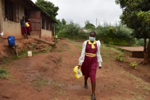 The Water Project: Givudemesi Primary School -  Pupils Carrying Water To School From Home