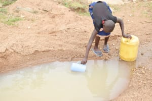 The Water Project: Kitile B Village Well -  Scooping Water
