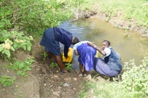 The Water Project: Mbiuni Primary School -  Students Collecting Water