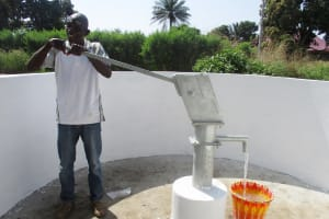 The Water Project: Lungi, Suctarr, #3 Lovell Lane -  Community Member Collecting Water After Installation