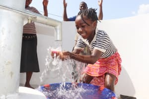 The Water Project: Lungi, Suctarr, #3 Lovell Lane -  Kid Joyfully Looking At Clean Water Flowing In Her Hands