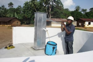 The Water Project: Lokomasama, Conteya Village -  Staff Collecting Water After Installing The Pump