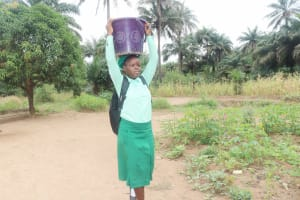 The Water Project: DEC Kitonki Primary School -  Student Carrying Water