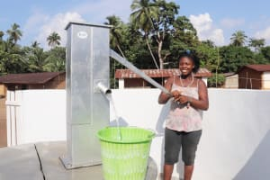 The Water Project: Lokomasama, Conteya Village -  Community Member Joyfully Collecting Water