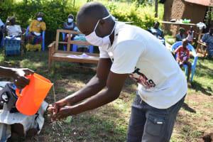 The Water Project: Musango Commnuity, Wabuti Spring -  Community Member Demonstrates Handwashing
