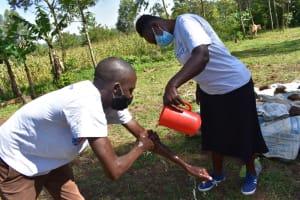 The Water Project: Musango Commnuity, Wabuti Spring -  Trainer Protus Demonstrates Handwashing Up To Elbows