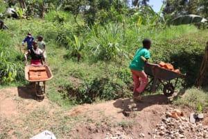The Water Project: Shianda Community, Panyako Spring -  Community Members Ferry Bricks To The Spring