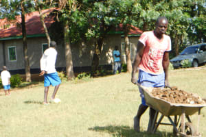 The Water Project: St. Peter's Ebunga'le Primary School -  Community Member Carrying Building Materials