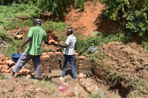 The Water Project: Maraba Community, Shisia Spring -  A Community Member Gives The Artisan A Helping Hand