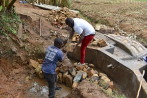 The Water Project: Mukhonje B Community, Peter Yakhama Spring -  Backfilling With Large Rocks
