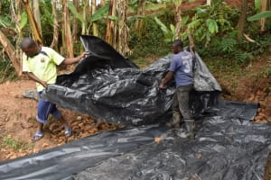 The Water Project: Mukhonje B Community, Peter Yakhama Spring -  Fitting The Tarp Over Backfilled Area