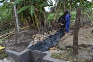 The Water Project: Kalenda A Community, Moro Spring -  Backfilling With The Tarp