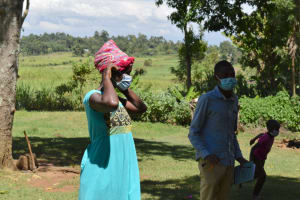 The Water Project: Kalenda A Community, Moro Spring -  A Woman Demonstrates How To Properly Put On A Mask