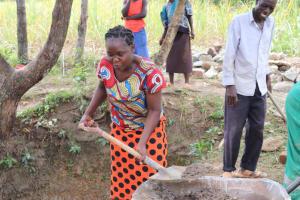 The Water Project: Luyeshe Community, Khausi Spring -  Madam Miriam Shoveling Concrete