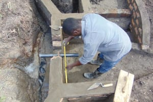 The Water Project: Makhwabuyu Community, Sayia Spring -  Setting The Pipe