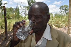 The Water Project: Makhwabuyu Community, Sayia Spring -  Boniface Drinking Water From The Protected Spring