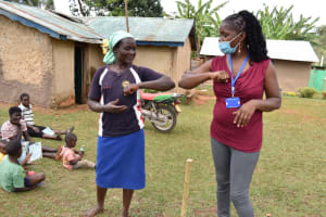 The Water Project: Mukhonje B Community, Peter Yakhama Spring -  Trainer Christine Demonstrates Alternative Contactless Greetings