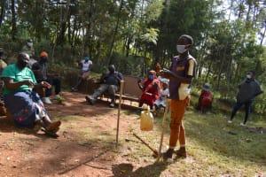 The Water Project: Shianda Community, Panyako Spring -  Mark Demonstrates Air Drying Hands After Washing